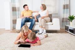 Enfants à l'aide du comprimé se trouvant sur le tapis Photo stock