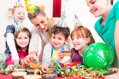 Enfants à la fête d'anniversaire avec les petits pains et le gâteau Images stock