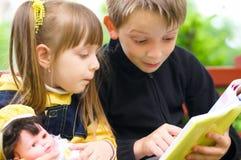 Enfants lisant le livre Photo stock