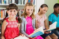 Enfants lisant un livre dans la bibliothèque Photos stock