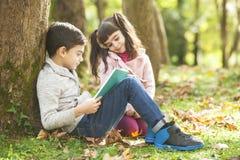 Enfants lisant un livre dehors Photographie stock libre de droits