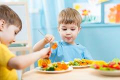 Enfants mangeant dans le jardin d'enfants Photos stock