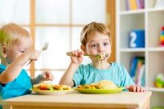 Enfants mangeant dans le jardin d'enfants Photo stock