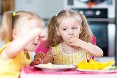 Enfants mangeant dans le jardin d'enfants ou à la maison Images stock