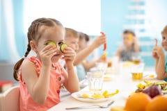 Enfants mangeant de la nourriture saine dans la garde photos libres de droits