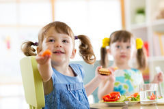 Enfants mangeant de la nourriture saine dans le jardin d'enfants ou à la maison Images libres de droits