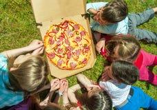 Enfants mangeant de la pizza images libres de droits