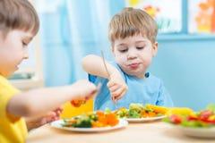 Enfants mangeant des légumes dans le jardin d'enfants ou à la maison Images libres de droits