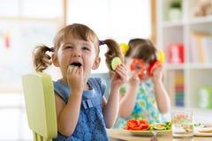 Enfants mangeant des légumes dans le jardin d'enfants ou à la maison Photographie stock libre de droits