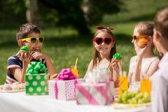 Enfants mangeant des petits gâteaux sur la fête d'anniversaire à l'été Images stock