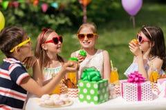 Enfants mangeant des petits gâteaux sur la fête d'anniversaire à l'été Photos libres de droits