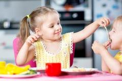 Enfants mangeant des spaghetti avec des légumes dans la crèche Photographie stock