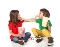 Enfants mangeant du maïs éclaté Image stock