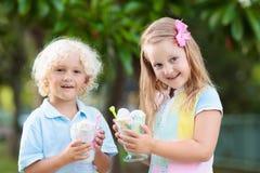 Enfants mangeant la crême glacée Enfant avec le dessert de fruit Photographie stock