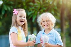 Enfants mangeant la crême glacée Enfant avec le dessert de fruit Image stock