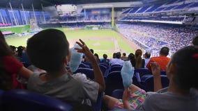 Enfants mangeant la sucrerie de coton aux stands pendant un jeu de baseball à un stade clips vidéos