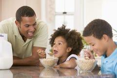 Enfants mangeant le déjeuner avec le papa Photographie stock libre de droits
