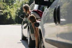 Enfants marchant par la route entre les voitures photographie stock libre de droits