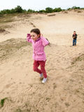 Enfants marchant par un paysage dunaire Image libre de droits