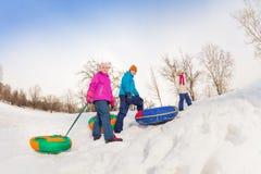 Enfants marchant vers le haut de la colline neigeuse avec les tubes colorés Image stock