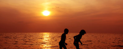 Enfants, mer et coucher du soleil Photographie stock libre de droits