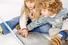 Enfants mettant en marche l'ordinateur image stock