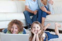 Enfants mignons à l'aide d'un ordinateur portable tandis que leurs parents observent Images stock