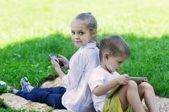 Enfants mignons à l'aide de la tablette et du smartphone Photographie stock libre de droits