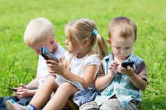 Enfants mignons à l'aide des smartphones Photo libre de droits