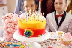 Enfants mignons célébrant l'anniversaire à la table image stock
