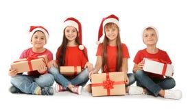 Enfants mignons dans des chapeaux de Santa avec des cadeaux de Noël sur le fond blanc Photos libres de droits