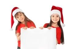 Enfants mignons dans des chapeaux de Santa avec l'affiche vide sur le fond blanc Célébration de Noël Image libre de droits