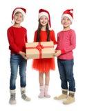 Enfants mignons dans des chapeaux de Santa avec le boîte-cadeau de Noël sur le fond blanc Image libre de droits