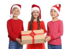 Enfants mignons dans des chapeaux de Santa avec le boîte-cadeau de Noël sur le fond blanc Image stock