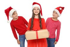 Enfants mignons dans des chapeaux de Santa avec le boîte-cadeau de Noël sur le fond blanc Photo libre de droits