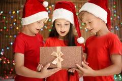 Enfants mignons dans des chapeaux de Santa ouvrant le boîte-cadeau de Noël sur le fond brouillé de lumières Photo libre de droits