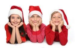 Enfants mignons dans des chapeaux de Santa sur le fond blanc Célébration de Noël Photographie stock libre de droits