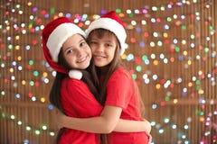 Enfants mignons dans des chapeaux de Santa sur le fond brouillé de lumières Célébration de Noël Images libres de droits