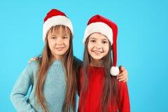 Enfants mignons dans des chapeaux de Santa sur le fond de couleur Célébration de Noël Photos libres de droits