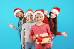 Enfants mignons dans des chapeaux de Santa sur le fond de couleur Célébration de Noël Images stock