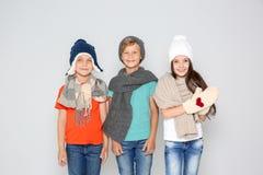 Enfants mignons dans des vêtements chauds posant sur le fond clair Célébration de Noël Images libres de droits