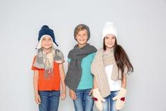 Enfants mignons dans des vêtements chauds posant sur le fond clair Célébration de Noël Images stock