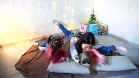 Enfants mignons de filles féminines et deux petites, posant pour l'appareil-photo et souriant, se trouvant sur des coussins, sur  banque de vidéos