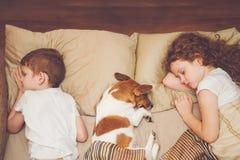 Enfants mignons et son chiot avec le sommeil photographie stock libre de droits