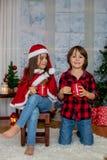Enfants mignons, garçon et fille, ayant l'amusement sur Noël Image stock