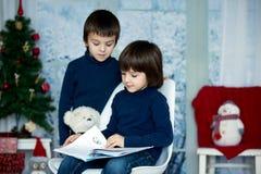 Enfants mignons, garçons, lisant un livre, se reposant sur une chaise Photo stock