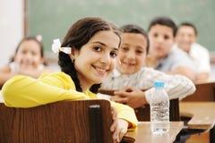 Enfants mignons heureux dans la salle de classe Photographie stock libre de droits