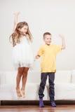 Enfants mignons heureux sauter de petite fille et de garçon Photo libre de droits