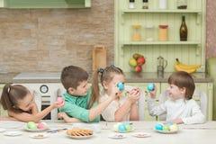 Enfants mignons jouant des oeufs de pâques à la table et au rire Image stock