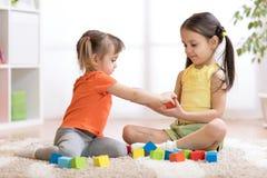 Enfants mignons jouant tout en se reposant sur le tapis à la maison Photo libre de droits